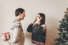 Szczęśliwa para wymienia prezenty w świątecznym roo w eleganckich pulowerach Zdjęcia Royalty Free