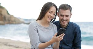 Szczęśliwa para wyszukuje telefon na plaży zdjęcie wideo