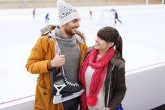 Szczęśliwa para z łyżwami na łyżwiarskim lodowisku Fotografia Stock
