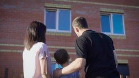 Szczęśliwa para z dzieckiem patrzeje nowego mieszkanie Kochająca rodzina w lato słonecznym dniu pokazuje chłopiec nowożytnego dom zbiory wideo