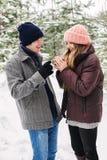 Szczęśliwa para z gorącymi napojami wśród jedlinowych drzew w śniegu Zdjęcia Royalty Free