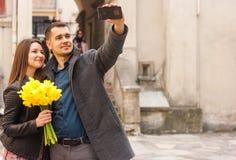 Szczęśliwa para z kwiatami robi selfie w ulicie kosmos kopii obrazy stock