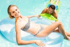 Szczęśliwa para z lilos w basenie Fotografia Royalty Free