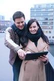 Szczęśliwa para z pastylka komputerem osobistym zdjęcie royalty free