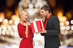 Szczęśliwa para z prezentem nad choinek światłami Obrazy Royalty Free