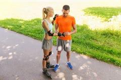 Szczęśliwa para z rolkowymi łyżwami jedzie outdoors Zdjęcia Stock