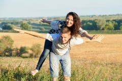 Szczęśliwa para z słonecznikami ma zabawę i odprowadzenie wzdłuż wiejskiej drogi, dziewczyny jazdy na jego i komarnicy outdoors,  Obraz Stock