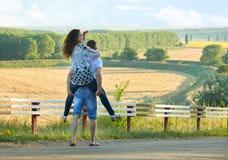 Szczęśliwa para z słonecznikami ma zabawę i odprowadzenie wzdłuż wiejskiej drogi outdoors, dziewczyny jazda na jego plecy - roman Obraz Royalty Free