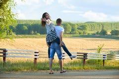 Szczęśliwa para z słonecznikami ma zabawę i odprowadzenie wzdłuż wiejskiej drogi outdoors, dziewczyny jazda na jego plecy - roman Zdjęcie Royalty Free