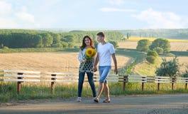 Szczęśliwa para z słonecznikami ma zabawę i odprowadzenie wzdłuż wiejskiej drogi romantycznej podróży, wycieczkować, turystyki i  Fotografia Stock
