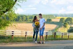 Szczęśliwa para z słonecznikami ma zabawę i odprowadzenie wzdłuż wiejskiej drogi romantycznej podróży, wycieczkować, turystyki i  Fotografia Royalty Free