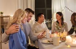 Szczęśliwa para z smartphone przy rodzinnym herbacianym przyjęciem obrazy royalty free