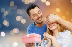 Szczęśliwa para z teraźniejszością nad światła tłem Zdjęcie Stock
