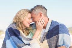 Szczęśliwa para zawijająca up w koc Zdjęcia Royalty Free