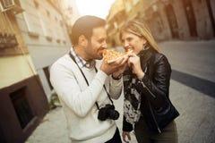 Szczęśliwa pary łasowania pizza outdoors zdjęcie royalty free