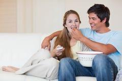 Szczęśliwa pary dopatrywania telewizja podczas gdy jedzący popkorn Fotografia Stock