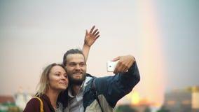 Szczęśliwa pary pozycja na centrum miasta na zmierzchu, bierze selfie fotografie z tęczą na tle na smartphone zbiory