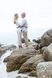 Szczęśliwa pary pozycja na skale i patrzeć each inny Obraz Stock