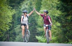 Szczęśliwa pary przejażdżka na halnej asfaltowej drodze na rowerach obraz royalty free