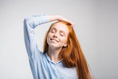 Szczęśliwa piękna dziewczyna ono uśmiecha się z zamkniętymi oczami dotyka jej czerwonego włosy Fotografia Royalty Free