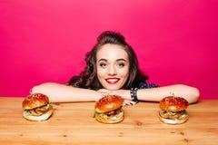 Szczęśliwa piękna dziewczyna z fryzurą z trzy hamburgerami na drewnianym Fotografia Stock