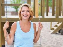 Szczęśliwa piękna kobieta ma zabawę na huśtawce fotografia royalty free