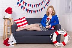 Szczęśliwa piękna kobieta w żeglarza jednolitym obsiadaniu w dekorującym li Obraz Royalty Free