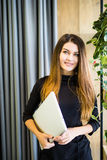 Szczęśliwa piękna kobiety pozycja przy biuro ścianą z notatnikiem interesy ilustracyjni ludzie jpg położenie Zdjęcia Royalty Free