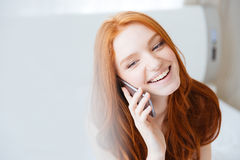 Szczęśliwa piękna młoda kobieta opowiada na telefonie komórkowym Obrazy Stock