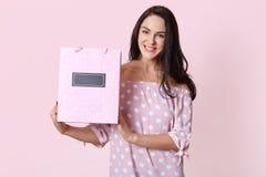 Szczęśliwa piękna młoda kobieta w polki kropki sukni trzyma torby na zakupy w jej rękach i ono uśmiecha się szczęśliwie, Studio s obrazy stock