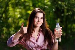 Szczęśliwa piękna młoda uśmiechnięta kobieta trzyma butelkę czysty wa Zdjęcia Stock