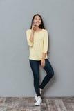 Szczęśliwa piękna młodej kobiety pozycja i opowiadać na telefonie komórkowym Obrazy Royalty Free