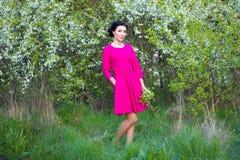 Szczęśliwa piękna marzycielska kobieta w menchiach ubiera w wiosny wiśni Gard Obraz Stock