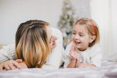 Szczęśliwa piękna matka i jej mała córka pozuje blisko choinki w wakacyjnym wnętrzu Obraz Royalty Free