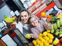 Szczęśliwa piękna matka i mała dziewczynka wybiera świeże owoc Obrazy Stock