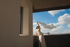 Szczęśliwa piękna panna młoda z latającą tkaniną nad niebem Obrazy Royalty Free