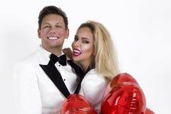 Szczęśliwa piękna para pozuje na białym tle i trzyma balony kierowi to walentynki dni obraz royalty free