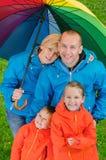 Szczęśliwa podeszczowa rodzina pod kolorowym parasolem Zdjęcie Stock