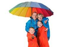 Szczęśliwa podeszczowa rodzina z parasola odosobnionym bielem Obrazy Stock