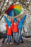 Szczęśliwa podeszczowa rodzina zabawę Zdjęcia Royalty Free