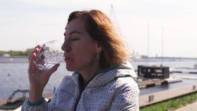 Szczęśliwa podróżnik woda pitna w restauracji - falisty brązu włosy, biała caucasian żeńska kobieta jest ubranym lekką kurtkę wew zbiory wideo