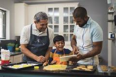 Szczęśliwa pokolenie rodzina używa cyfrową pastylkę w kuchni podczas gdy przygotowywający jedzenie Zdjęcie Stock