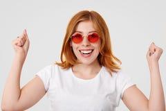 Szczęśliwa pomyślna imbirowa młoda kobieta utrzymuje zaciskać pięści podnosi, toothy uśmiech, świętuje pomyślnego dzień, ubierają obraz stock