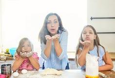 Szczęśliwa potomstwo matka i daughtesr dolewania mąka przez arfy dla fotografia royalty free