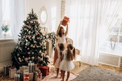Szczęśliwa potomstwo matka i jej dwa powabna córka w ładnych sukniach zdjęcie royalty free