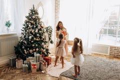 Szczęśliwa potomstwo matka i jej dwa powabna córka w ładnych sukniach obraz royalty free