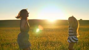 Szczęśliwa potomstwo matka, piękny mały blondynki córki doskakiwanie w pszenicznym polu i ono uśmiecha się, zmierzch w tle zbiory