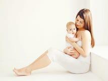 Szczęśliwa potomstwo matka z dzieckiem w białym pokoju w domu zdjęcie royalty free