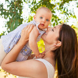 Szczęśliwa potomstwo matka z dzieckiem wydaje czas plenerowego na lecie Zdjęcia Stock