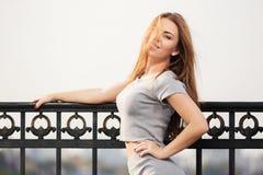 Szczęśliwa potomstwo mody kobieta przy ciskającym żelaza ogrodzeniem Zdjęcia Royalty Free